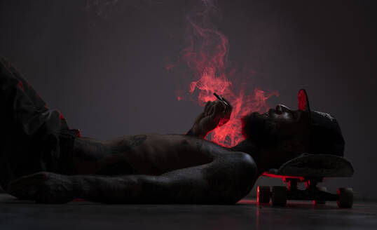 Tattooed skateboarder lying on the floor smoking a joint - AMUF00111