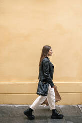 Young woman with shopping bags walking in the city - GRCF00233