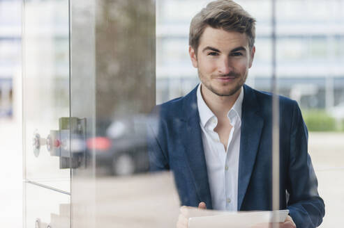 Portrait of young businessman using tablet in the city - DIGF10918