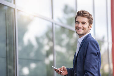 Happy young businessman holding smartphone at an office building - DIGF10924