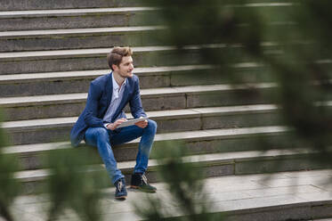 Young businessman sitting on stairs using tablet - DIGF10930