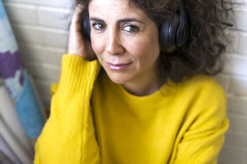 Portrait of smiling woman listening to music with headphones - ERRF03805