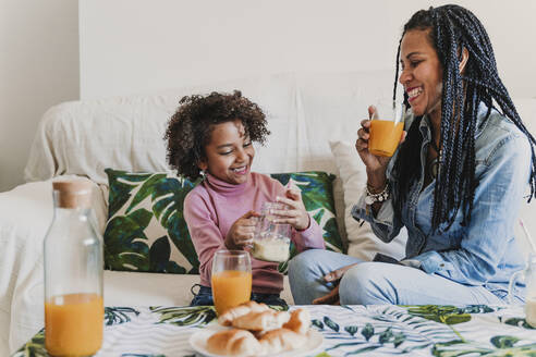 Happy mother and her little daughter drinking smoothie and juice at home - EBBF00012