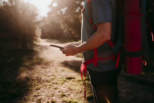 Close-up of man with smartphone on a hiking trip - EBBF00020
