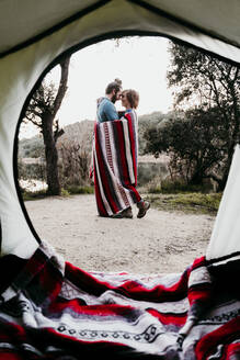 Couple wrapped in a blanket camping at lakeside - EBBF00041