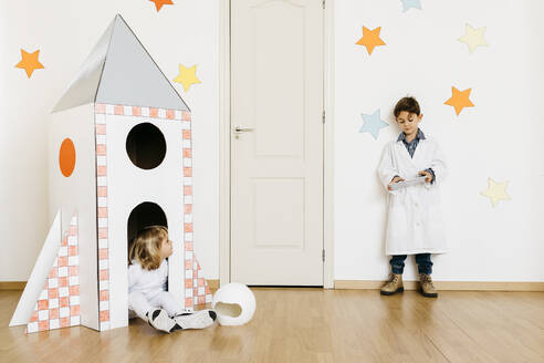 Siblings playing astronaut and researcher at rocket - JRFF04448