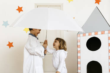 Siblings playing astronaut and researcher with umbrella at rocket - JRFF04463