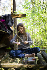 Girl carving a piece of wood sitting on raised hide in the woods - LVF08888