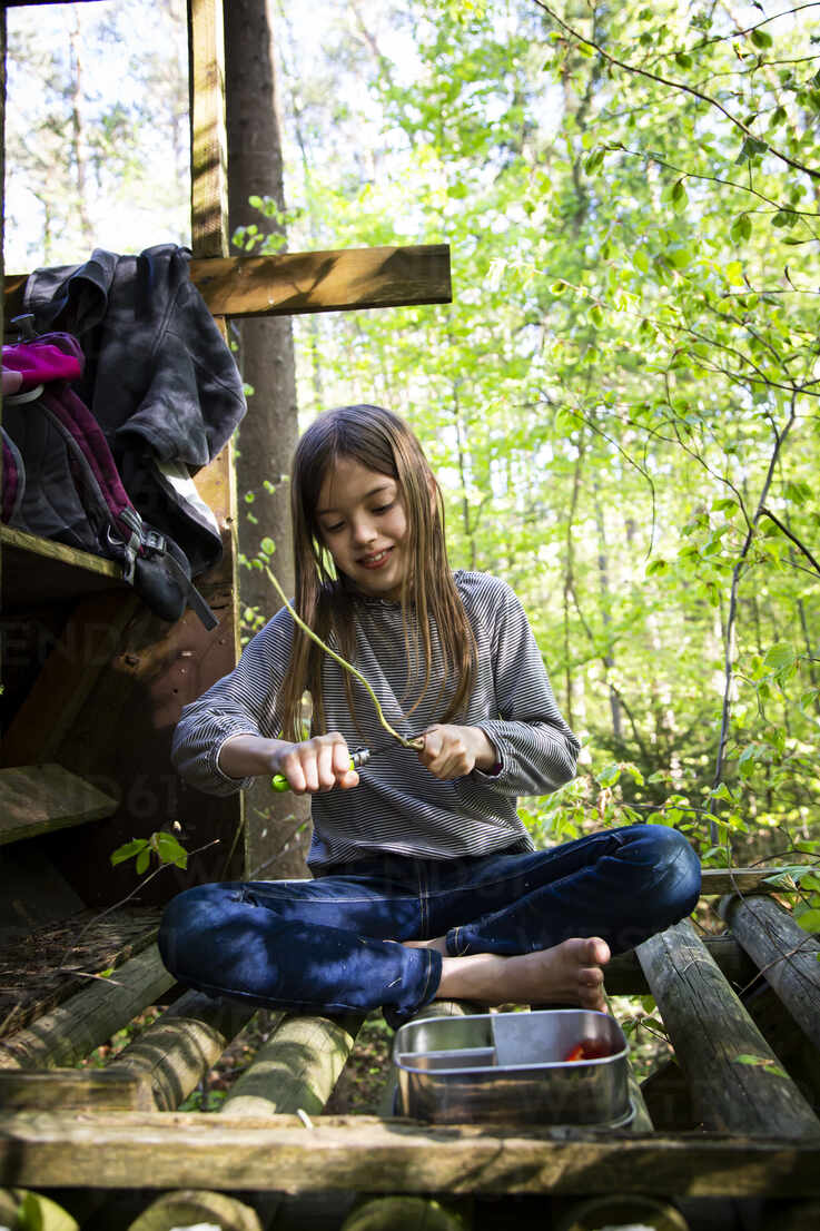 Girl carving a piece of wood sitting on raised hide in the woods - LVF08888 - Larissa Veronesi/Westend61