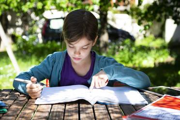 Girl sitting at garden table doing homework - LVF08891
