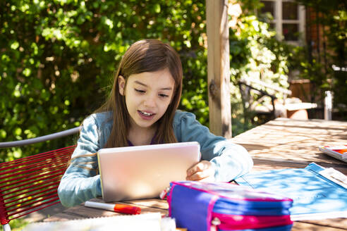 Girl sitting at garden table doing homework and using tablet - LVF08894
