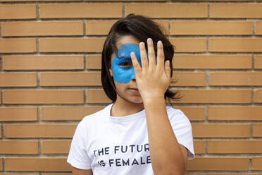 Portrait of boy with painted blue mask on his face wearing t-shirt with imprint 'The Future is Female' - VABF02927