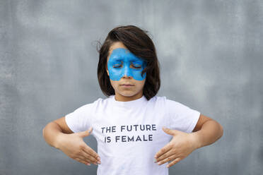 Portrait of boy with painted blue mask on his face wearing t-shirt with imprint 'The Future is Female' - VABF02930