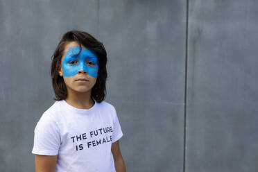 Portrait of boy with painted blue mask on his face wearing t-shirt with imprint 'The Future is Female' - VABF02936