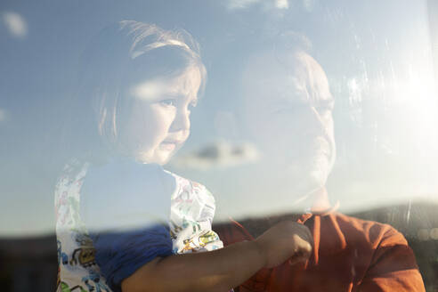 Portrait of father and little daughter behind windowpane looking at distance - VABF02939