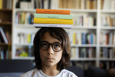 Portrait of boy balancing stack of books on his head - VABF02951