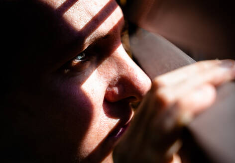 Adult woman with blue eyes opening a wooden curtain with her fingers to look through the window while the sunlight creates sun and shadow on her face. Horizontal photo. - CAVF80967