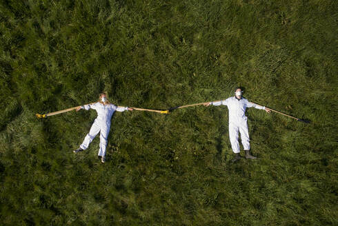 High angle view of two people wearing hazmat suits lying on a lawn during Corona virus crisis, demonstrating social distancing with wooden sticks. - CUF55380