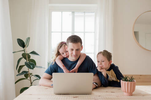 Parent working from home with kids climbing on him - CAVF81217