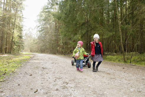 Two little sisters pulling trolley on forest track - BRF01454