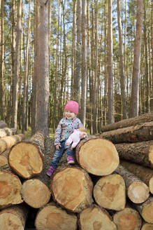 Smiling little girl with doll sitting on stack of wood in the forest - BRF01457