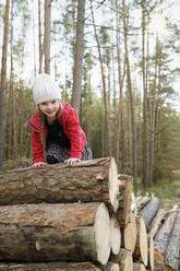 Portrait of happy little girl climbing on stack of wood in the forest - BRF01460