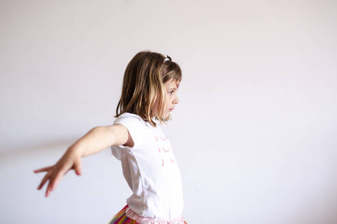 Happy girl with skirt and shirt dancing at home - CAVF81502