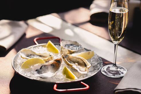 Plate with oysters, lemon and ice and a glass of champagne - CAVF81514