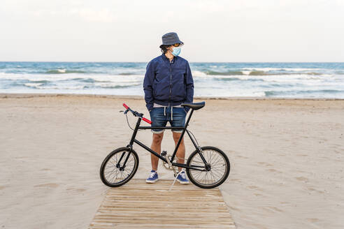 Mature man with bicycle, standing on the beach, wearing face mask - DLTSF00685