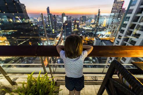 Girl looking at skyline of Bangkok at dusk, Thailand - GIOF08185