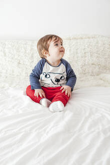 Portrait of baby boy sitting on bed looking up - FLMF00218