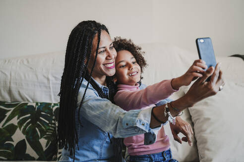 Happy mother and her little daughter taking selfie with smartphone at home - EBBF00083