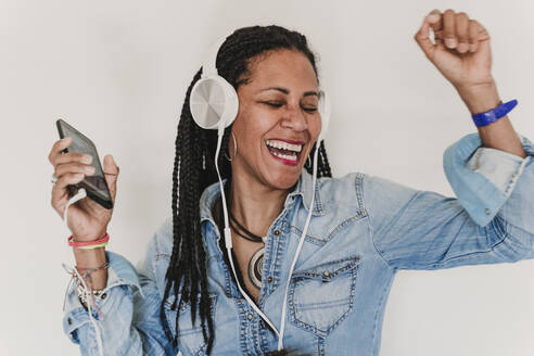 Portrait of dancing woman listening music with headphones and smartphone - EBBF00095
