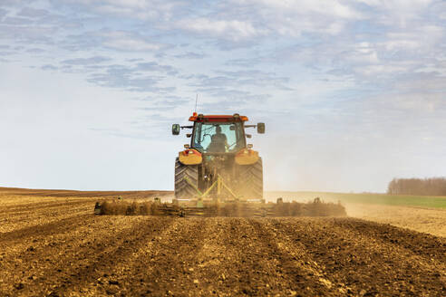 Back view of farmer in tractor plowing field in spring - NOF00094
