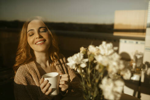 Happy blond woman at home drinking coffe in the kitchen in the morning - GMLF00197