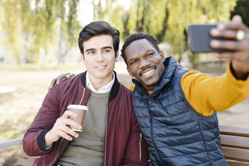 Two happy young men sitting on park bench taking a selfie - JCZF00094