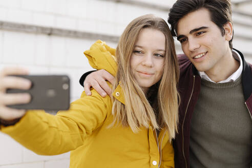 Portrait of smiling young couple taking a selfie - JCZF00103