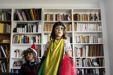 Portrait of boy dressed up as a rock star in the living room with his younger brother - VABF02964