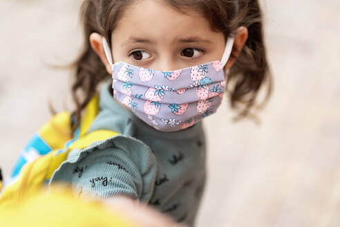 Girl with mask holding father's hand outdoors - EGAF00108