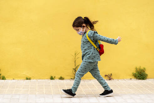 girl walking with backpack and mask outdoors - EGAF00114