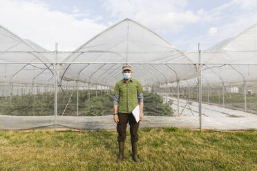 Farmer with mask in front of the organic greenhouse - MRAF00568