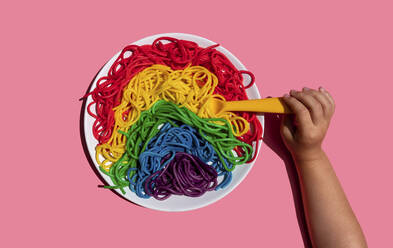 Child eating colorful rainbow spaghetti pasta for kids on with yellow fork on pink background - GEMF03734
