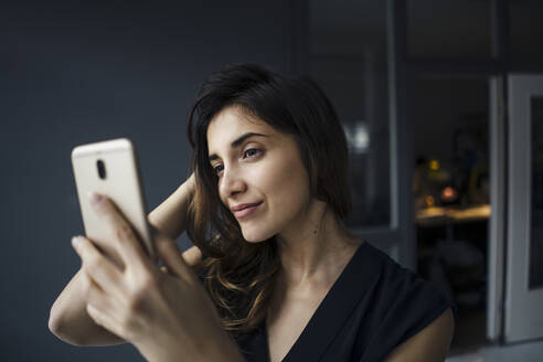 Portrait of smiling young woman taking selfie with smartphone - JOSEF00747