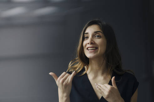 Portrait of gesturing young businesswoman against grey background - JOSEF00762