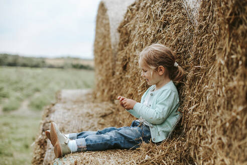 Little girl sitting on straw bales - VBF00069