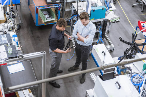 Two men having a meeting in factory examining product - DIGF10951