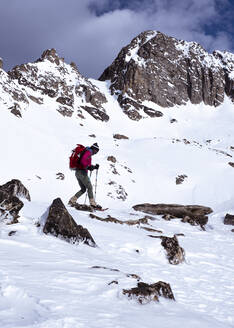 Woman snowshoe hiking in snow covered mountains in winter in Montana - CAVF81866