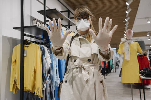 Woman with face mask and disposable gloves shopping in a fashion store - AHSF02586