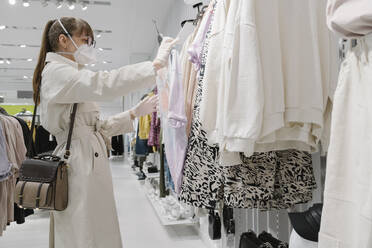 Woman with face mask and disposable gloves shopping in a fashion store - AHSF02589