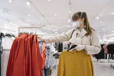 Woman with face mask and disposable gloves shopping in a fashion store - AHSF02592